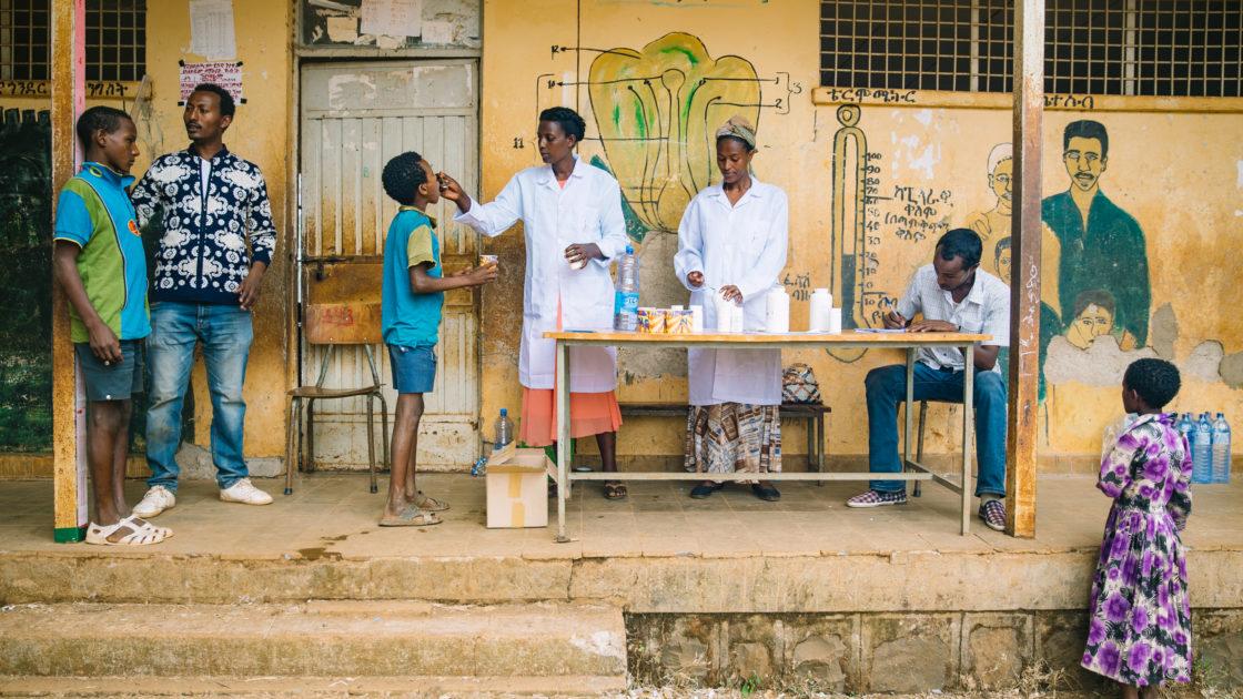 Village elder giving meds to a preteen child